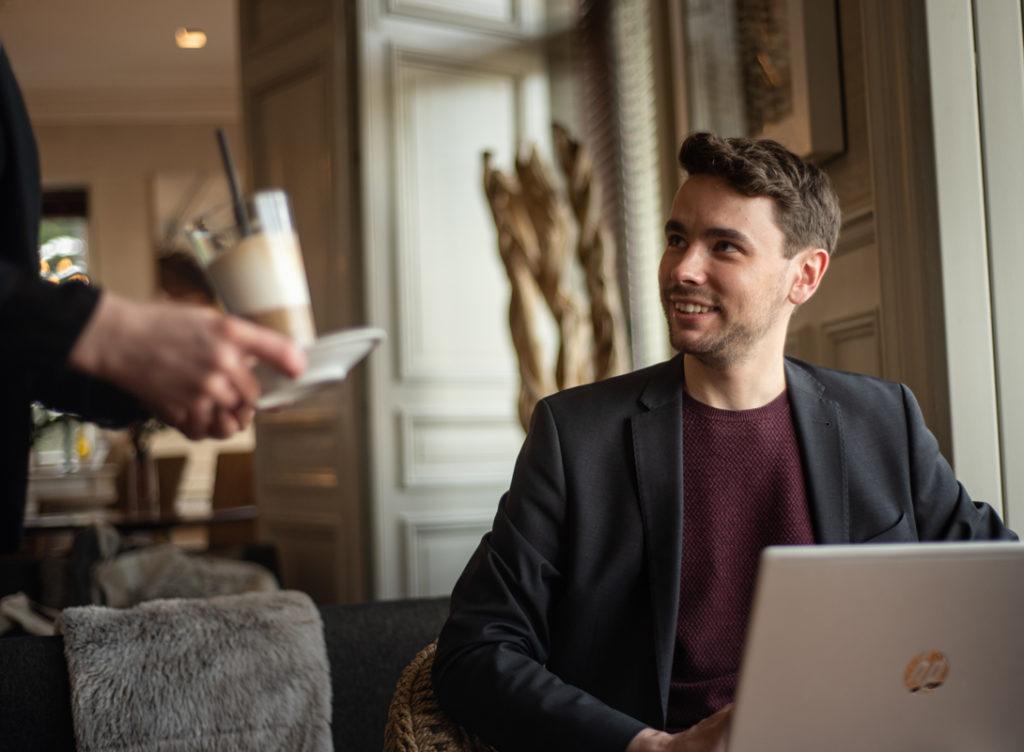Homme prenant une boisson au salon